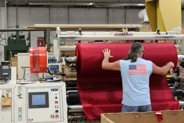 Nylon is added to a custom slitting machine to cut the width needed for the stripes on the American flag at the Coschocton, Ohio Annin Flag Company.