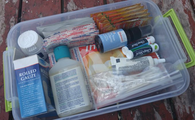 Restocking a first aid kit for camping.