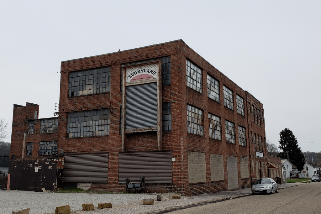 The World's Largest Washboard hangs on the side of a brick building.