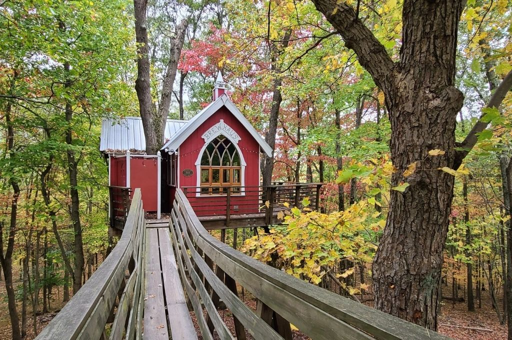 adorable red treehouse that stands out against the trees