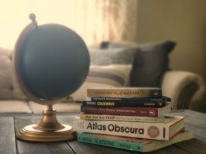 A stack of road trip books and a globe.