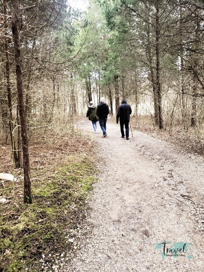 Three people walking along a wooded trail.
