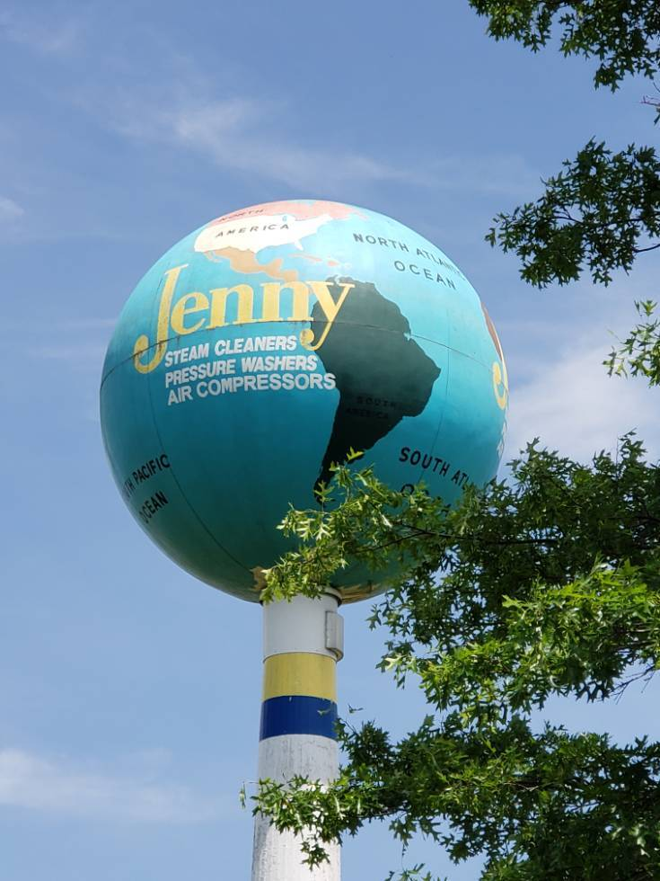The Jenny Globe is visible through a couple trees in the parking area.