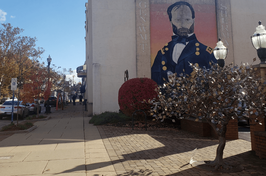 The Tree of Life stands in front of the Sherman mural in Lancaster.