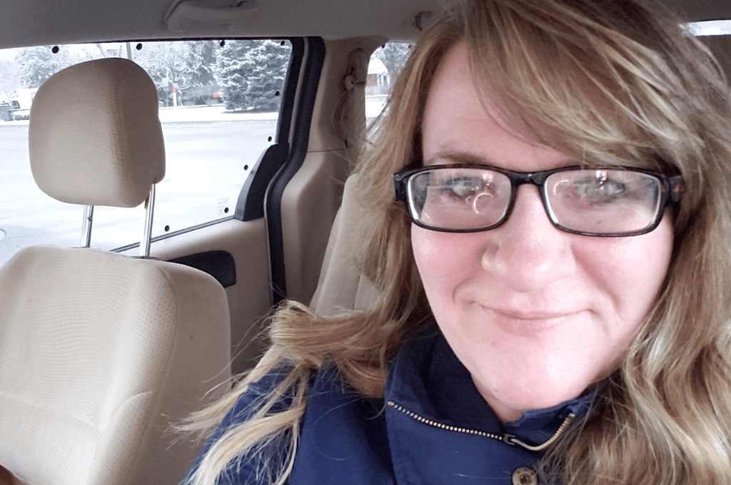 A woman with long dark blond hair, wearing a blue jacket and dark rimmed glasses, is in a vehicle, traveling alone.