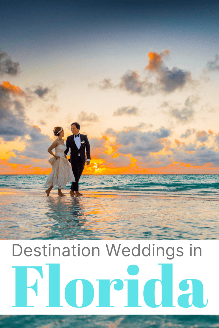 A newly married couple walking along the beach at sunset.