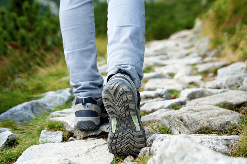 A hikers feet in tennis shoes as they walk along a rocky path.