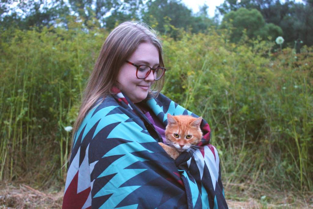 A young woman in a field holding an orange cat who is peeking out from the blanket.