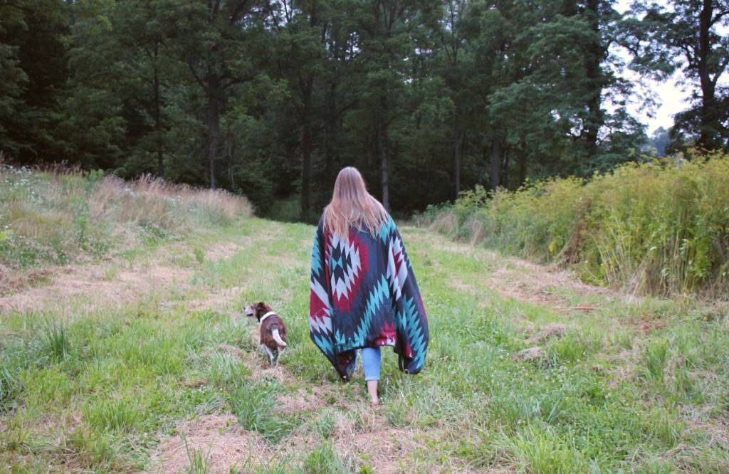 A young woman walking in a field towards a wooded area with a Native American print Kachula blanket from Coalatree with a dog.