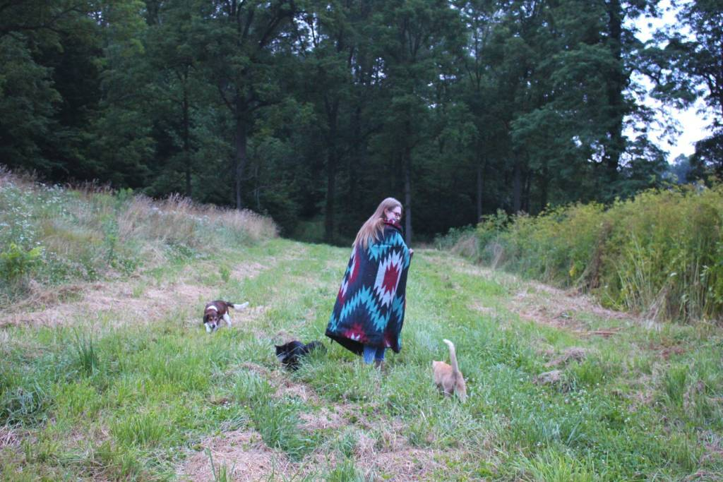 A young woman walking in a field surrounded by a dog and two cats. She is wrapped in a Kachula blanket.