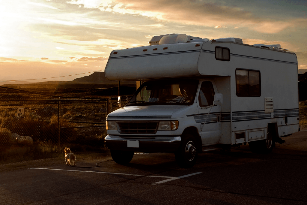 A Class C RV parked outside a fence that says Pet Area with a dog outside as the sun begins to set.