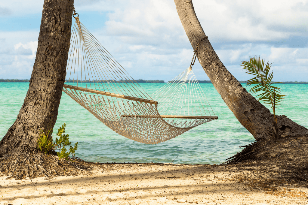 A hammock strung between two trees on the beach with a view of gorgeous turquoise water.