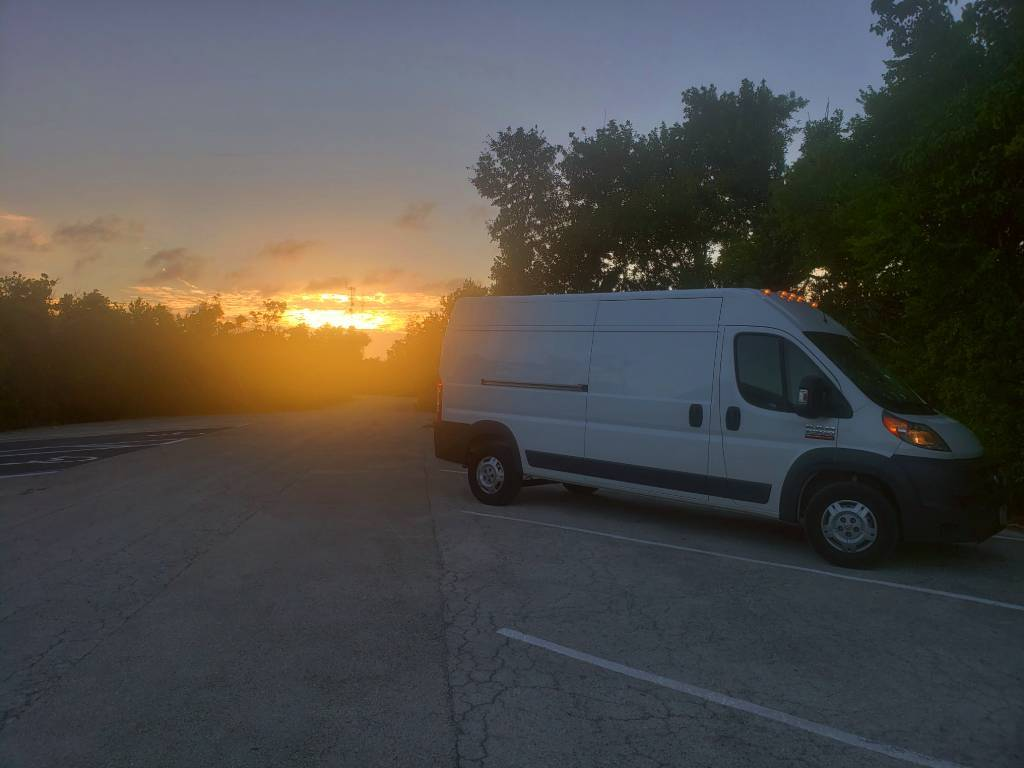A cargo van parked in a parking lot with the sun setting behind it.