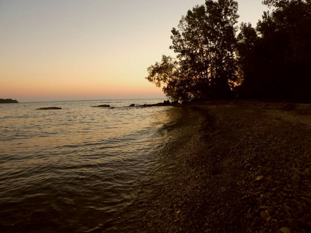 The sun is rising over the water on Lake Erie.
