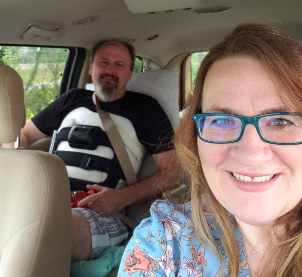 Two smiling people in a vehicle.