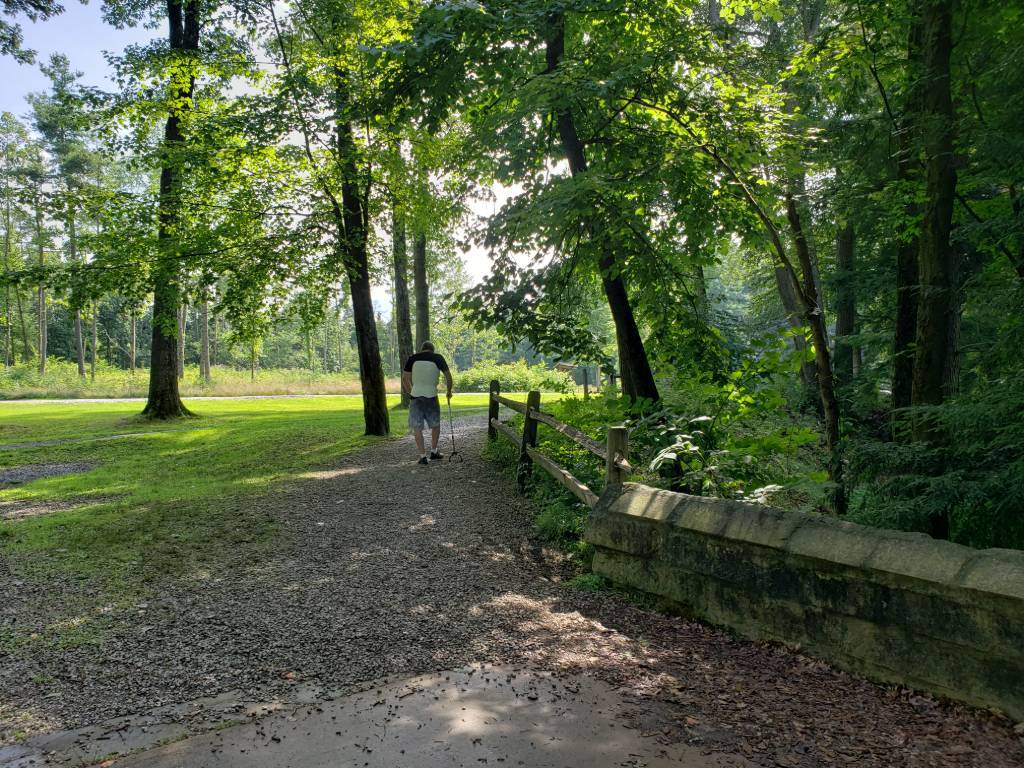 Man walking along a trail in a wooded area.