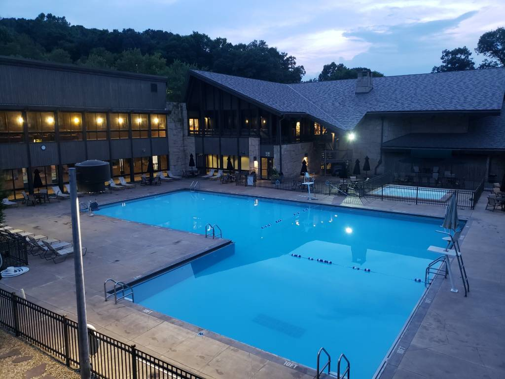 A beautiful indoor pool that is outside as the sun goes down.