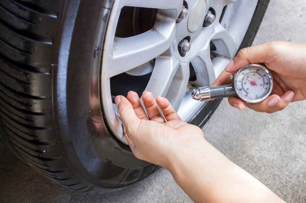 A person checking the tire pressure in a tire on their vehicle.