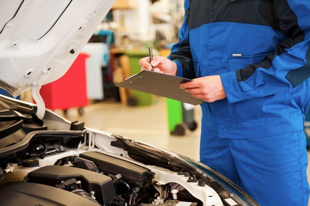 A mechanic looks at a car.