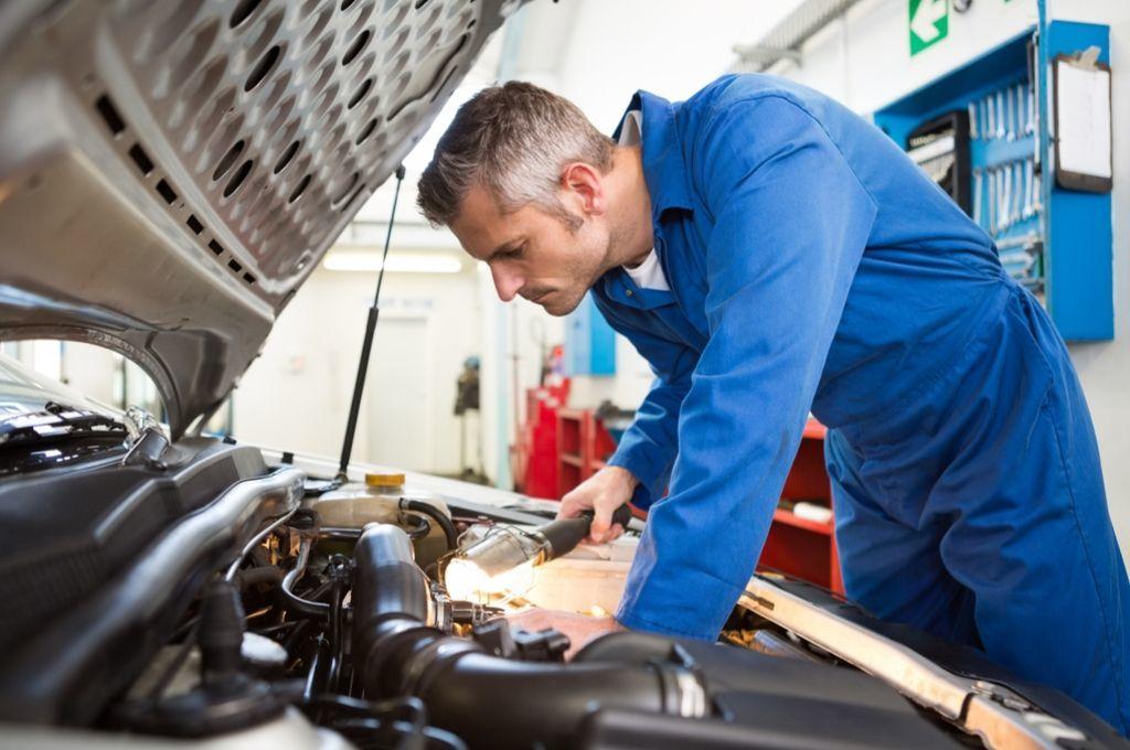 A mechanic inspecting a motor.