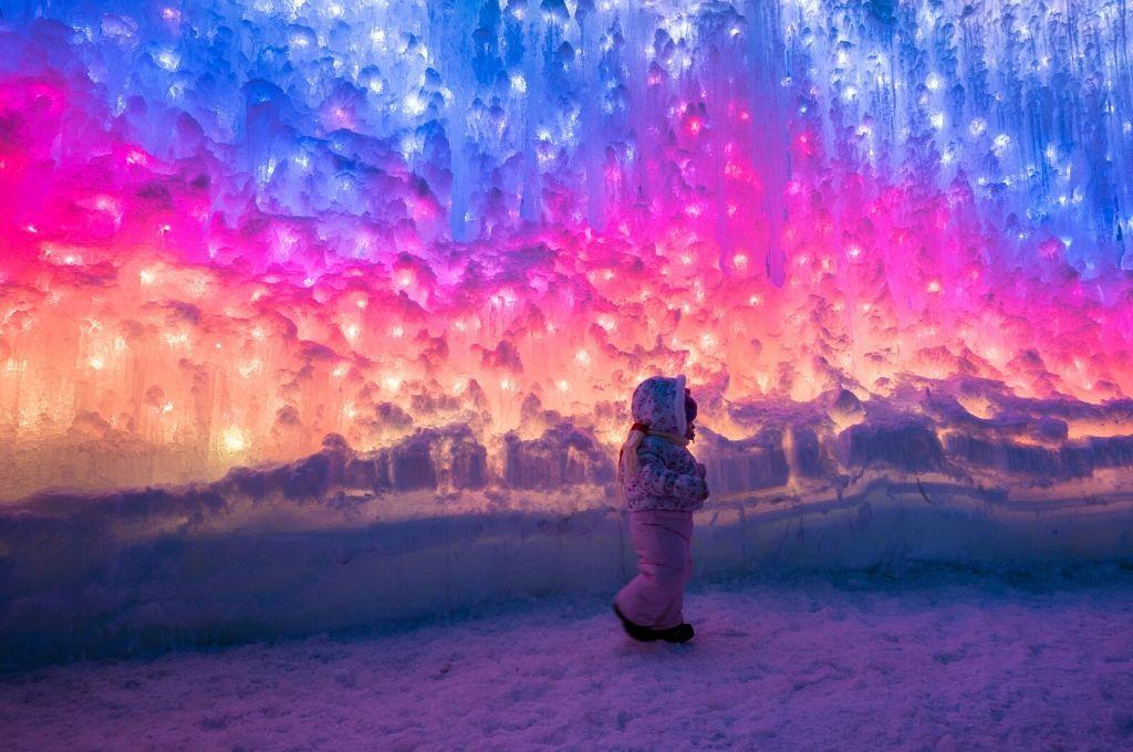 A little girl walking inside an ice castle
