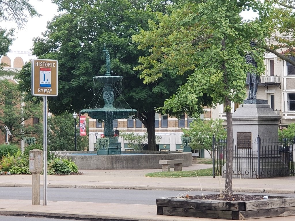 A sign for the Lincoln Highway located on the square in Downtown Mansfield with a fountain and monument in the background.