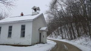 A white schoolhouse from the 1800s on a dirt road.