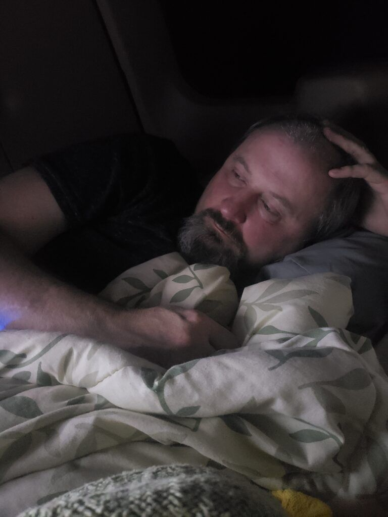 A man watching tv curled up with a comforter.