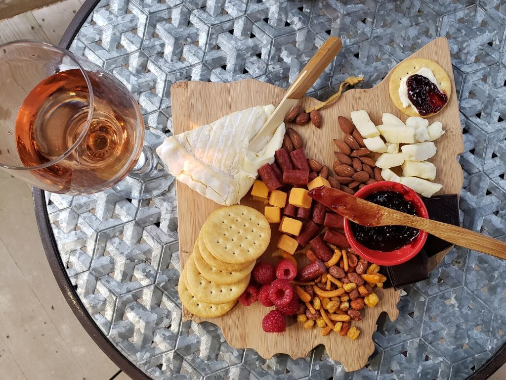 A glass of wine sits beside an Ohio shaped charcuterie board