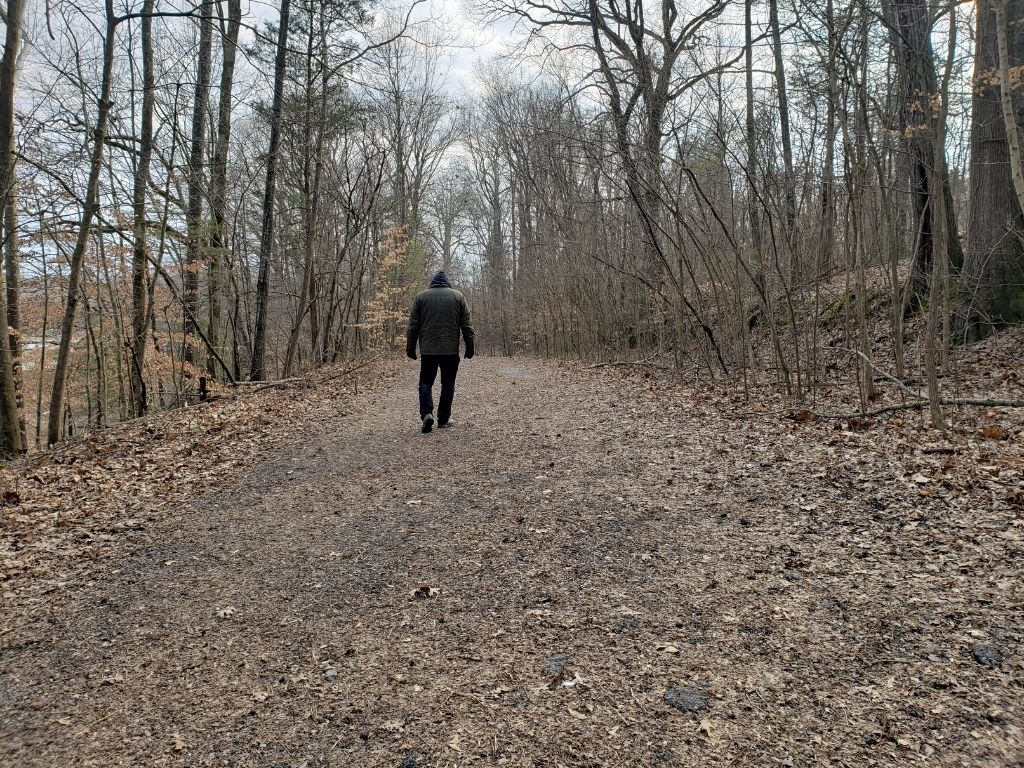 man walking along a wooded trail