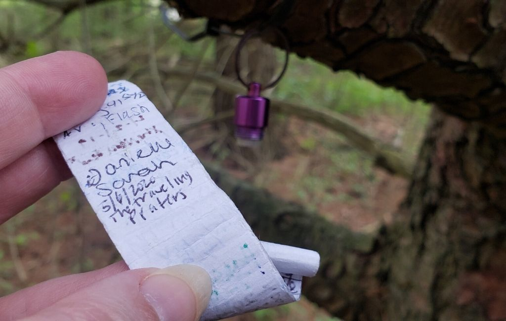 A small geocache hanging from a tree that was hard to find.