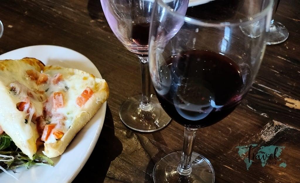 A glass of red wine and bruschetta.