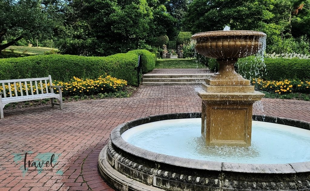 An ornate water fountain in a formal garden setting.