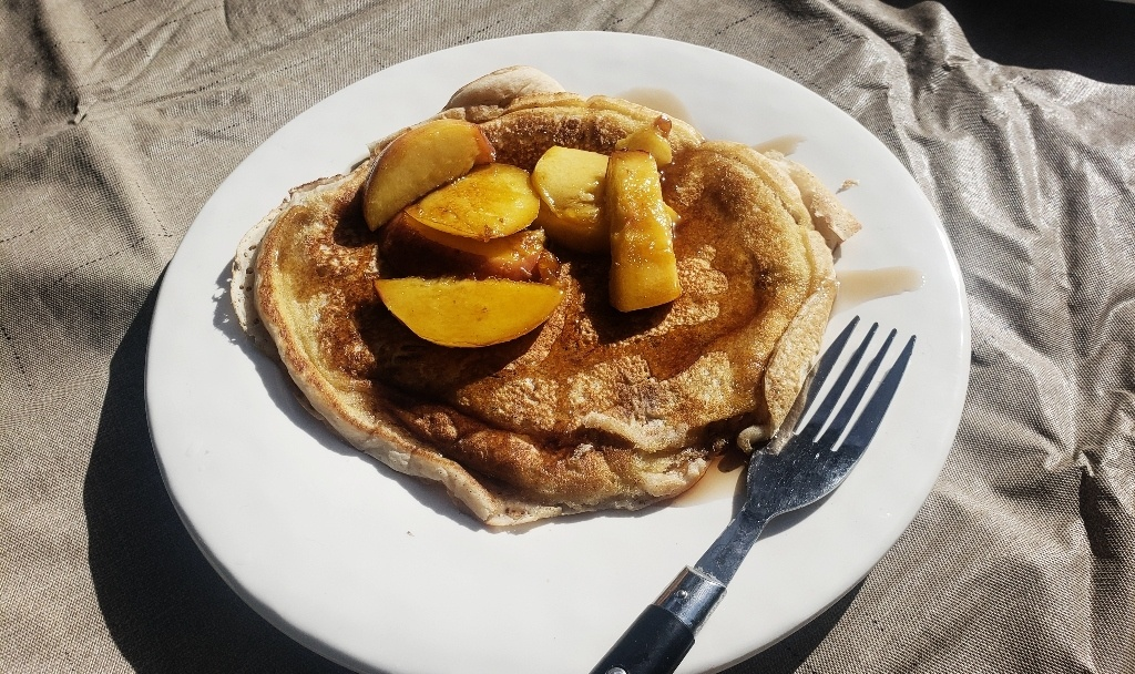 A plate of pancakes with peaches.