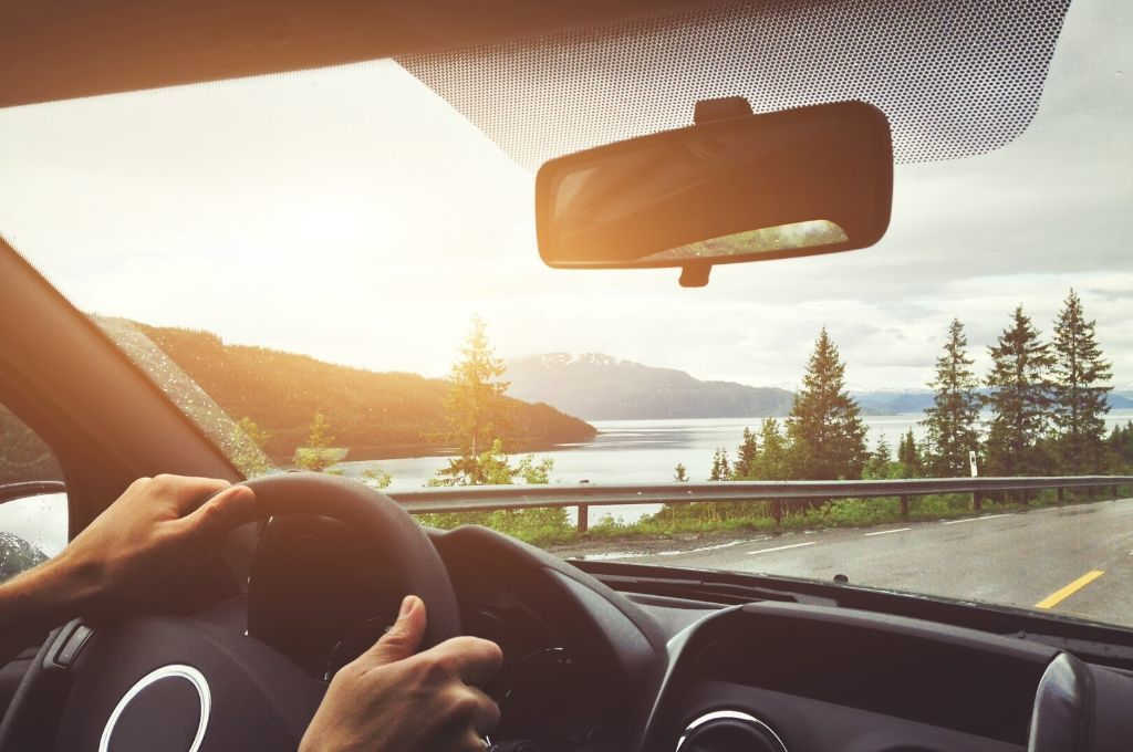 A driver driving along a scenic highway with views of a lake and pine trees.