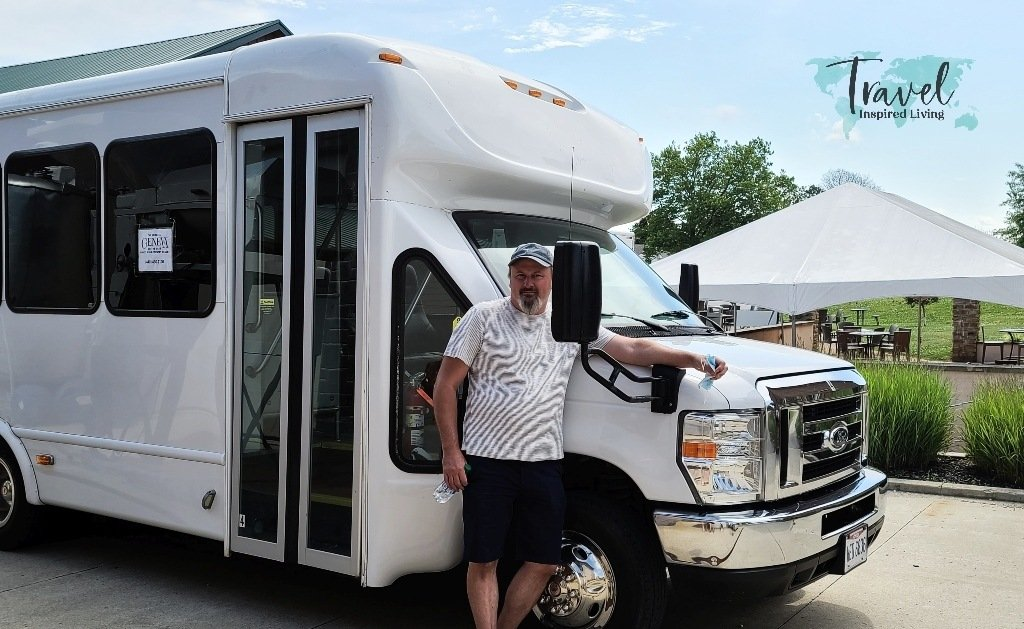 A white shuttle bus with man standing beside it.