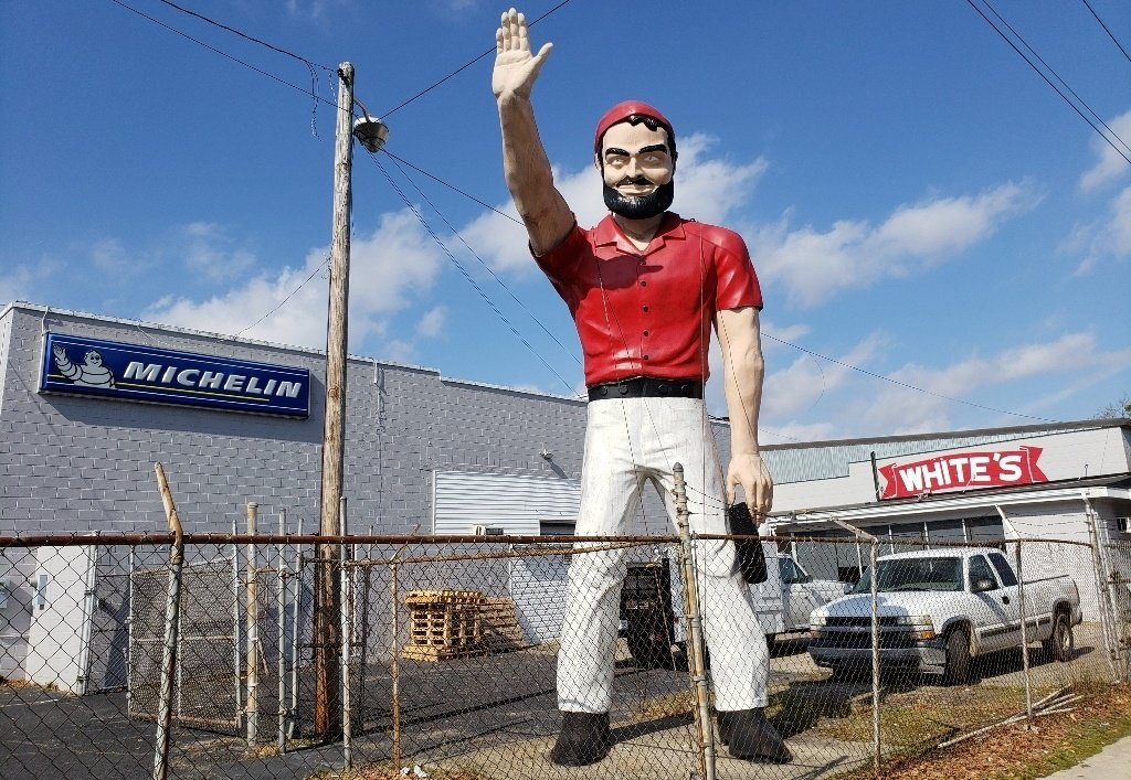 A muffler man at a Michelin tire shop wearing white pants and a red shirt.