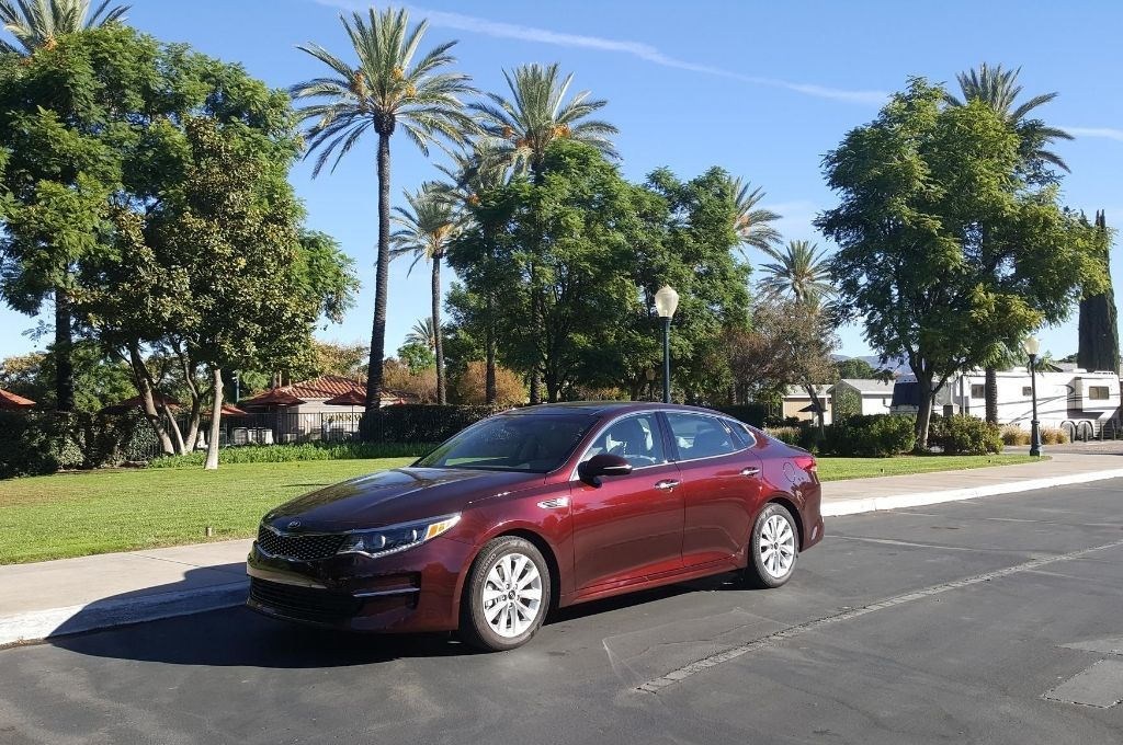 A nice burgundy sedan with palm trees in the background.