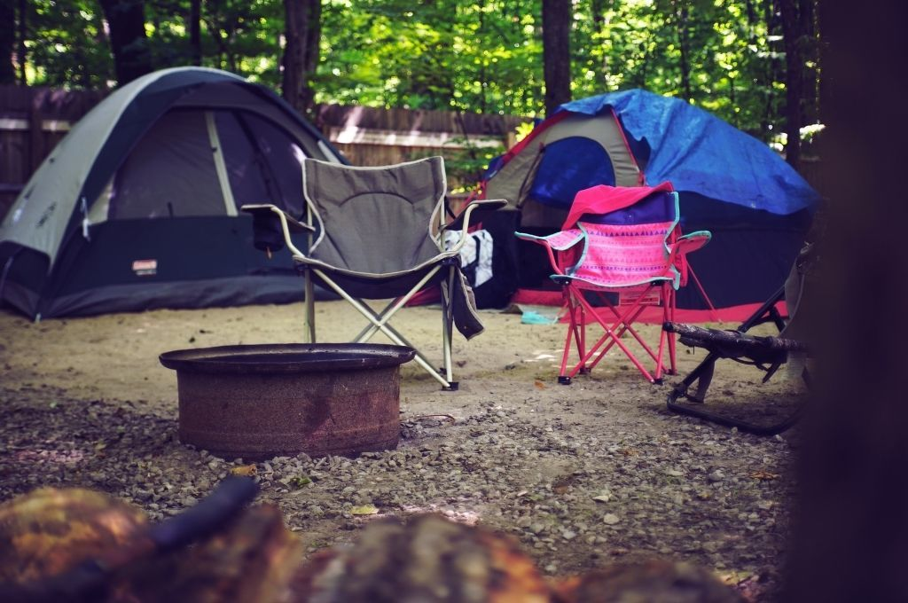 Tents with camping chairs around a fire ring with no fire.
