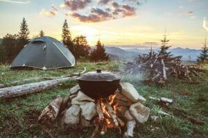 A tent with a campfire and large pile of wood.