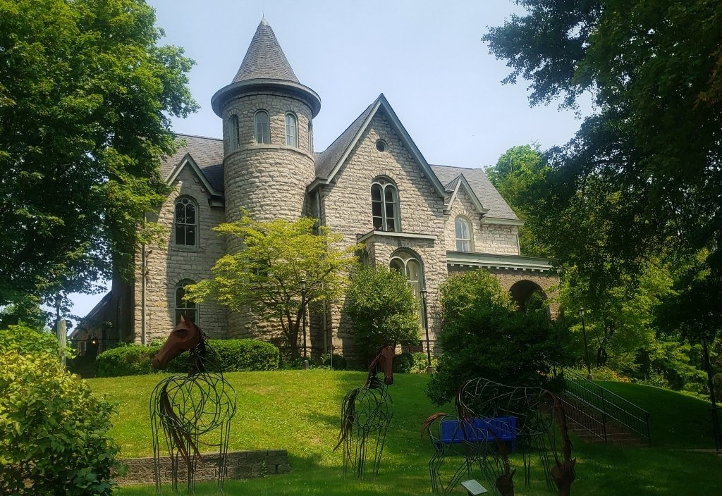 A stone building that resembles a castle with metal work horses in the front yard