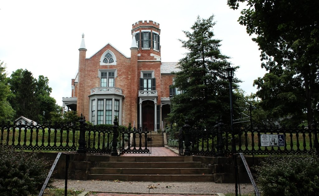 A brick building with a turret that resembles a castle behind a black iron fence..