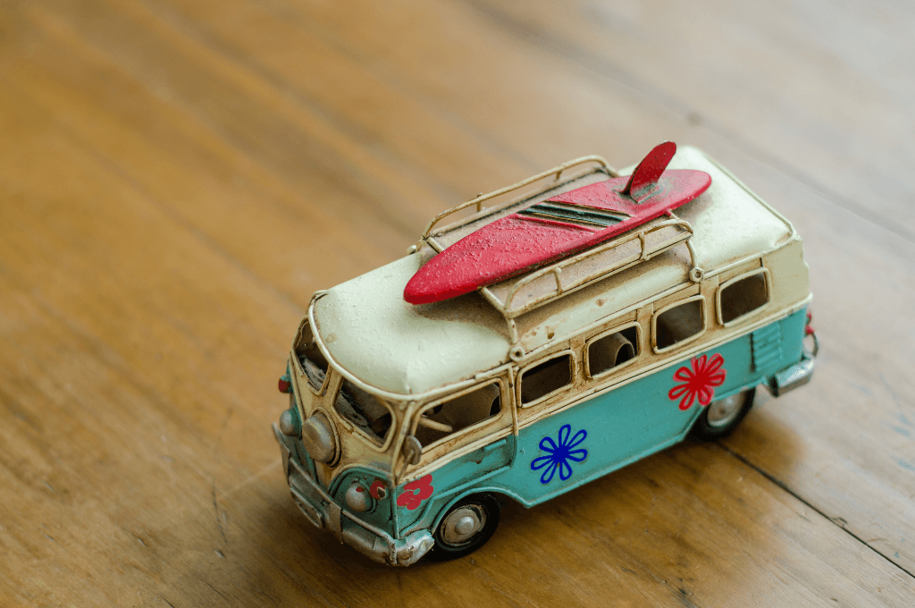 a toy van with a surfboard on top