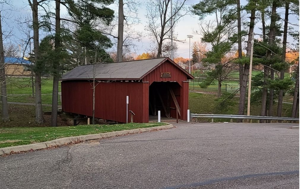 A covered bridge in a wooded area.
