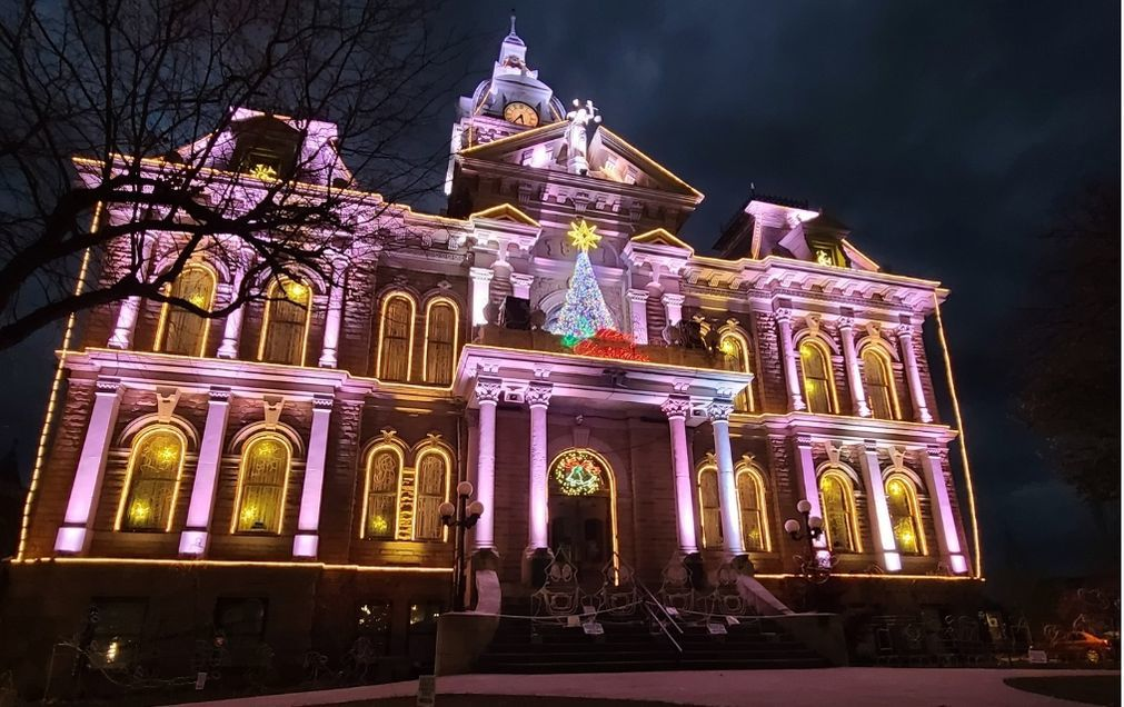 An historic courthouse lit with Christmas lights.