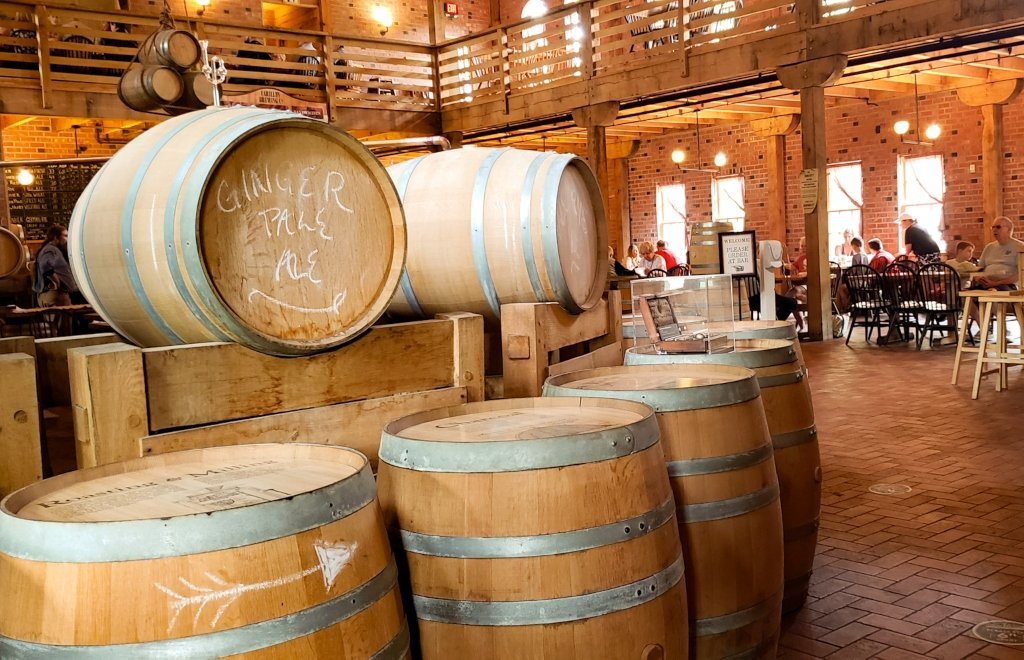 Wooden barrels inside the Carillon Brewing Company with people seated at tables in the background.