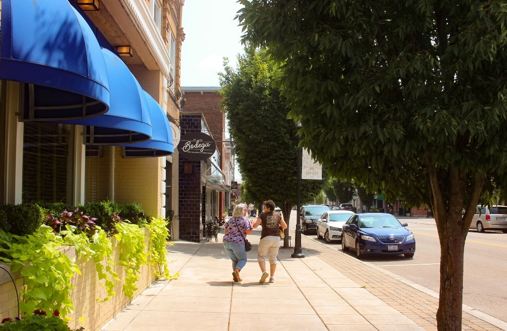 Two women laughing and walking down the street.