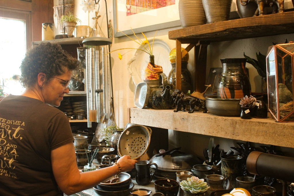 A woman looking at pottery in a store.