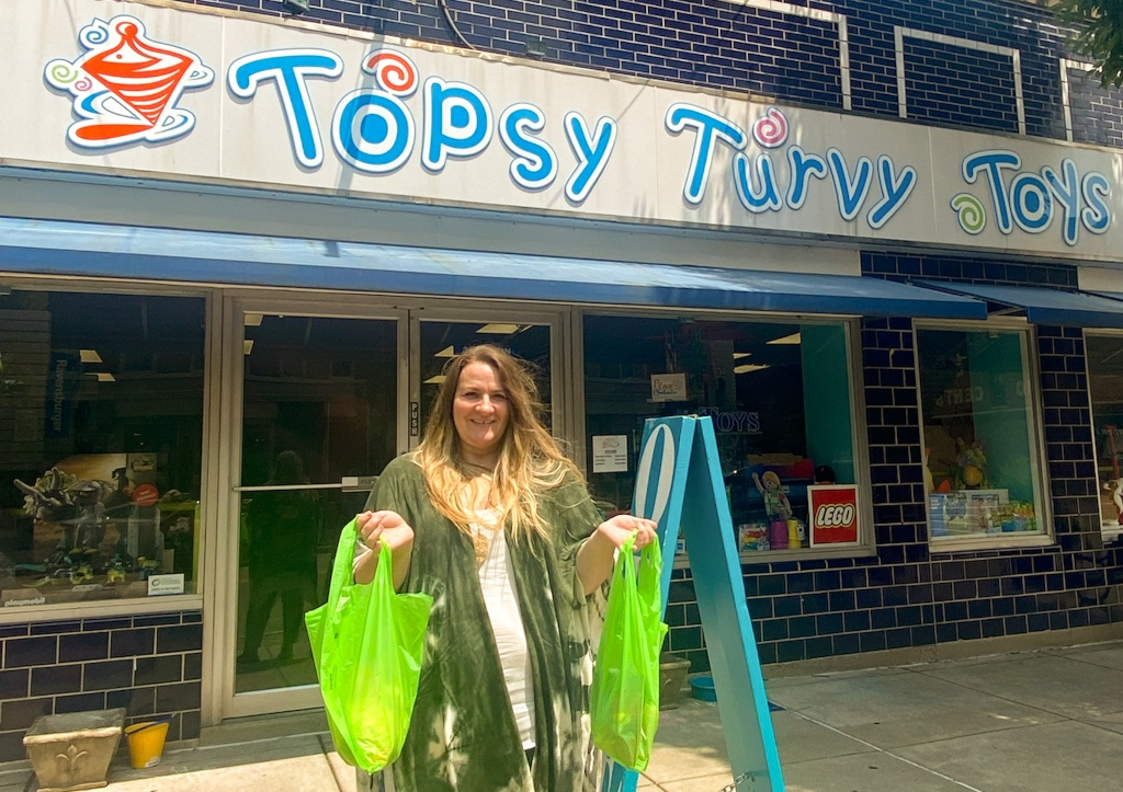 A woman standing outside a toy store holding up shopping bags of purchases.