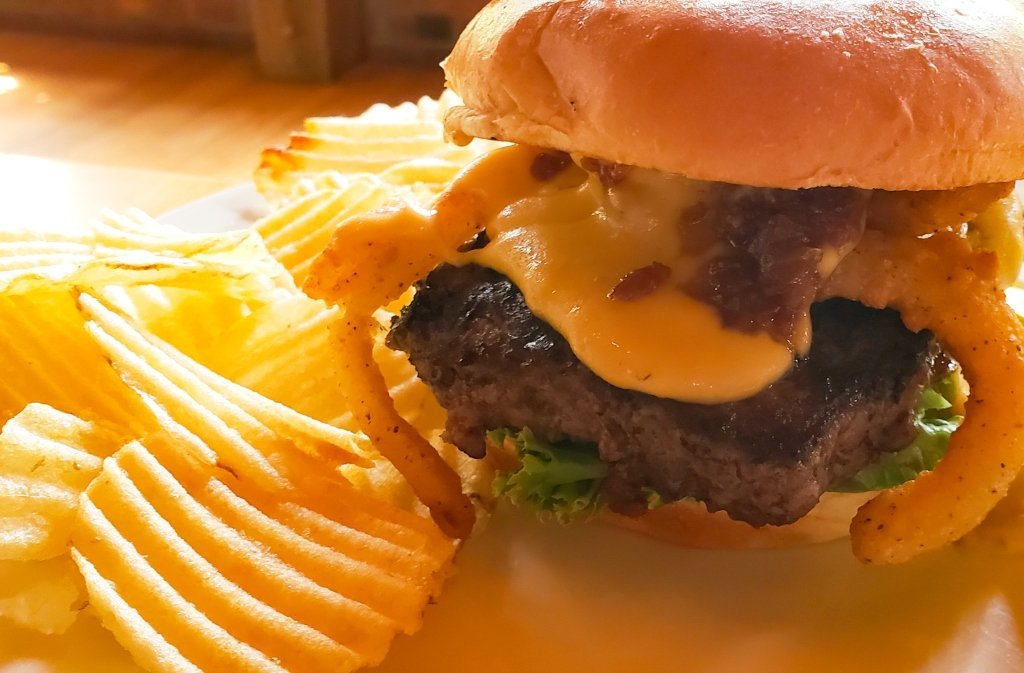 A burger with beer cheese and potato chips.